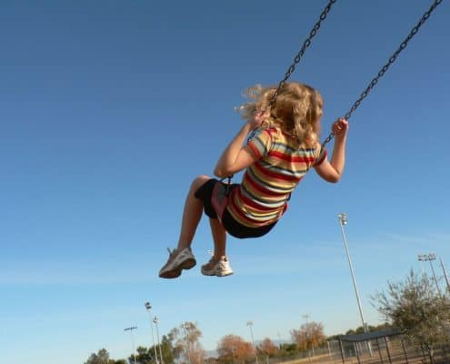 girl flying high on a swingset at the park