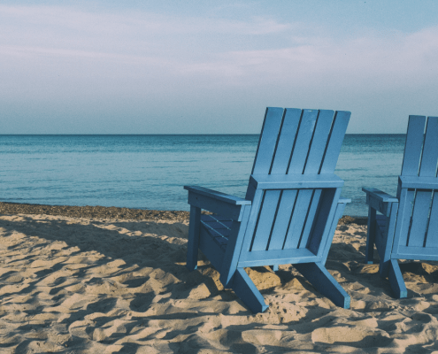 two blue chairs on the beach facing the ocean