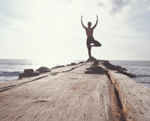 woman in tree pose at the end of a pier